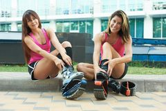 Two women put on kangoo jumping boots and smiles. beautiful girls wearing shoes before outdoor fitness workout. Active lifestyle concept stock image