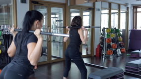 Two women raising bar on shoulders inside sport gym stock video