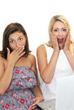 Two women reacting in shocked awe. Two women reacting in unison with expressions of shocked awe as they raise their hands to their faces isolated on white Stock Photography