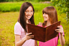 Two women read a book Stock Photo
