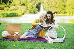 Two women reading book in the park Royalty Free Stock Image
