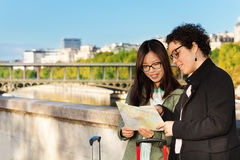 Two women reading map at the embankment of Seine Stock Photos