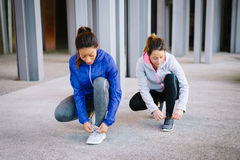 Two women ready for running. Two female athletes ready for urban running. Women getting ready for fitness workout and exercising Stock Images