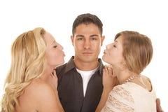 Two women ready to kiss man close Stock Photo