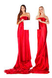 Two women in red dress with magazine in hands Royalty Free Stock Photos