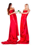 Two women in red dress with present in hands looking to each oth Stock Image
