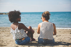 Two women relaxing on beach talking Stock Image
