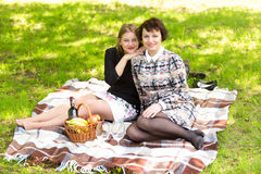 Two women relaxing on blanket at park and having picnic Stock Images