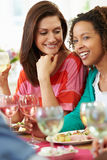 Two Women Relaxing At Dinner Party. Close Up Of Two Women Relaxing At Dinner Party Holding Glass Of White Wine Royalty Free Stock Images