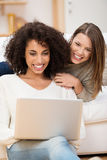 Two women relaxing at home with a laptop Stock Photos