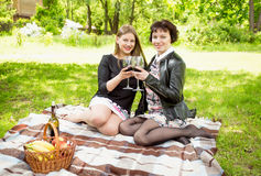 Two women relaxing on picnic and drinking wine Stock Photos