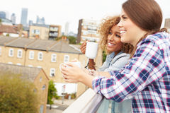 Two Women Relaxing On Rooftop Garden Drinking Coffee Royalty Free Stock Photos
