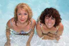 Two women relaxing in the swimming pool on holidays Royalty Free Stock Image