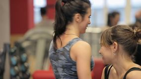 Two women relaxing and talking after workout in gym. Two girls talk in the gym. Girls laugh between exercise machines in. Two women relaxing and talking after stock video footage