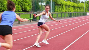 Two women in relay race stock footage