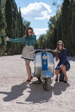 Two women on road with vintage motorcycle Royalty Free Stock Photos