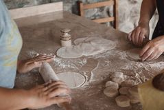 Two women roll out the dough on a wooden table. The frame is only women`s hands. Two women roll out the dough. On a wooden table are round blanks of dough. The Royalty Free Stock Photos