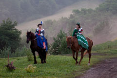 Two women in the royal baroque dress riding Royalty Free Stock Photos