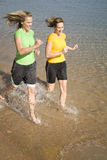 Two women run in water. Two women splashing in the water while they run Royalty Free Stock Image