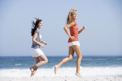 Two women running along beach Stock Photos