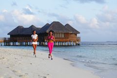 Two women running on beach Royalty Free Stock Images