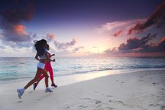 Two women running on beach. Fitness sport women running on beach at sunset Stock Photography