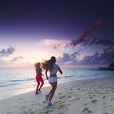 Two women running on beach Stock Photo