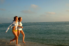 Two women running on beach. Two young women running on the beach Stock Image