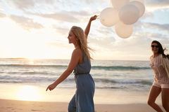 Two women running on the beach with balloons. Young beautiful women running on the beach holding balloons with her friend. Friends with balloons on the beach stock photo