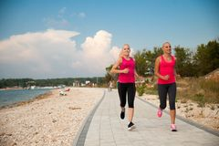 Two women athlets running on the beach - early morning summer w. Two women running on the beach - early morning summer workout royalty free stock photos