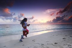 Two women running on beach stock images