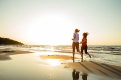 Two women running on beach. Two women running and jumping on beach royalty free stock photos