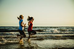 Two women running on beach. Two women running and jumping on beach stock photos
