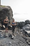 Two women running on the beach near rocks stock photos