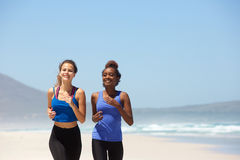 Two women running at the beach in summer Royalty Free Stock Photo