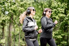 Two women running in the park royalty free stock photo