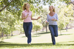 Two women running in park and smiling Stock Photography