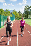 Two Women Running on Track Together Stock Photos