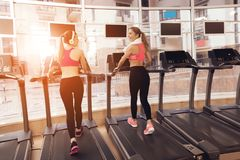 Two women running on treadmill at the gym. They look happy, fashionable and fit. Two women in sportswear running on treadmill at the gym. They look happy Stock Photo