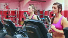 Two women running on treadmills. In gym stock footage