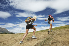 Two Women Running Up Hill. Rear view of two women running up hill against cloudy sky Stock Photos