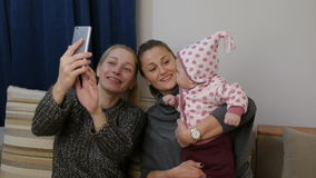 Two women 40s is making selfie with little baby and smiling while sitting on sofa at home. Two women 40s is making selfie with her adorable little baby and stock footage
