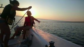 Two women sailing yacht, enjoying sea voyage, beautiful sunset, active rest. Stock footage stock video