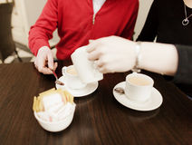 Friends with cups of coffee. Two women sat at table pouring cups of coffee Royalty Free Stock Images