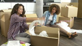 Two Women Sealing Boxes Ready For House Move. Two women packing breakables into cardboard box ready for move. Shot on Sony FS700 in PAL format at a frame rate of stock footage