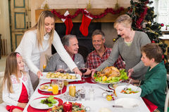 Two women serving christmas dinner to their family Stock Photo