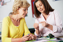 Two Women Sewing Quilt Together. And Talking Royalty Free Stock Photo