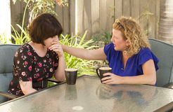 Two women sharing and chatting over coffee. Women and friendship sharing stories over a cup of coffee outdoors Royalty Free Stock Images