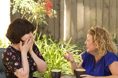 Two women sharing and chatting over coffee. Women and friendship sharing stories over a cup of coffee outdoors Stock Photo