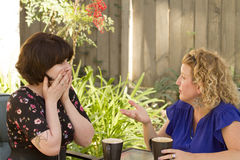 Two women sharing and chatting over coffee. Women and friendship sharing stories over a cup of coffee outdoors Royalty Free Stock Photo